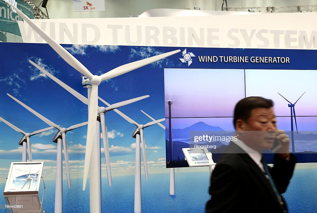 An attendee uses a mobile phone as he walks past a wind turbine model at the Hyundai Heavy Industries Co. booth at the 22nd World Energy Congress (WEC) in Daegu, South Korea, on Monday, Oct. 14, 2013. The WEC, a global conference on the energy market, will run until Oct. 17. Photographer: SeongJoon Cho/Bloomberg via Getty Images