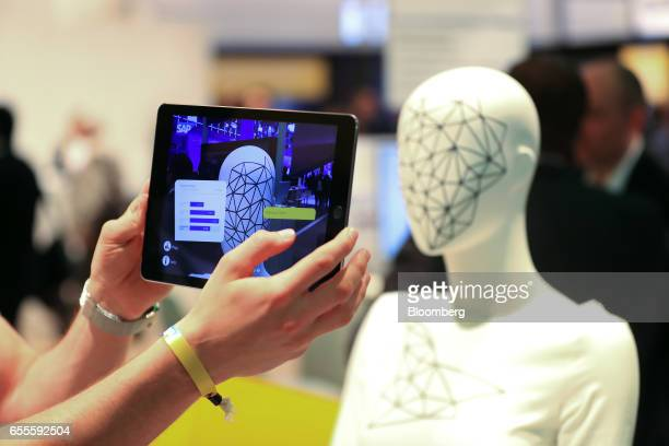 An attendee uses a SAP CoPilot digital assistant in the SAP SE pavilion at the CeBIT 2017 tech fair in Hannover Germany on Monday March 20 2017...