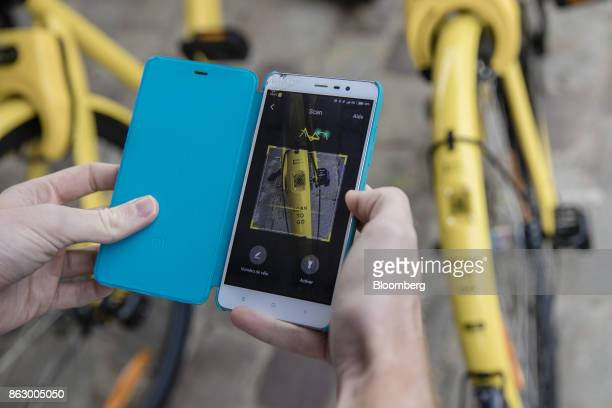 An attendee uses a smartphone app to scan a Quick Response code on a Ofo Inc hire bicycle during a presentation at the Autonomy urban mobility summit...