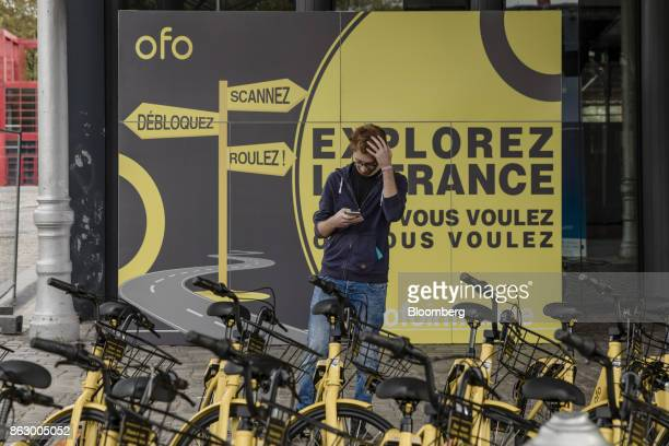 An attendee uses a smartphone beside parked Ofo Inc hire bicycles during a presentation at the Autonomy urban mobility summit in Paris France on...