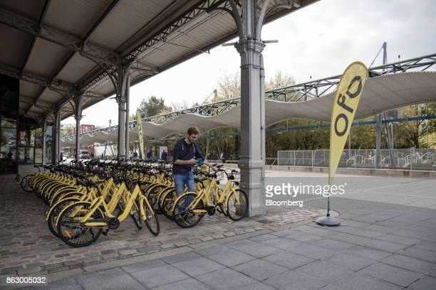 An attendee uses a smartphone beside rows of parked Ofo Inc hire bicycles during a presentation at the Autonomy urban mobility summit in Paris France...