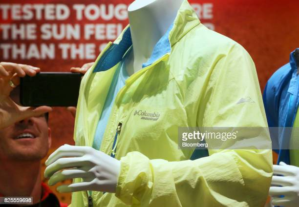 An attendee uses a smartphone device to take a photograph of a Columbia Sportwear Co jacket on display during the Outdoor Retailer Summer Market Show...