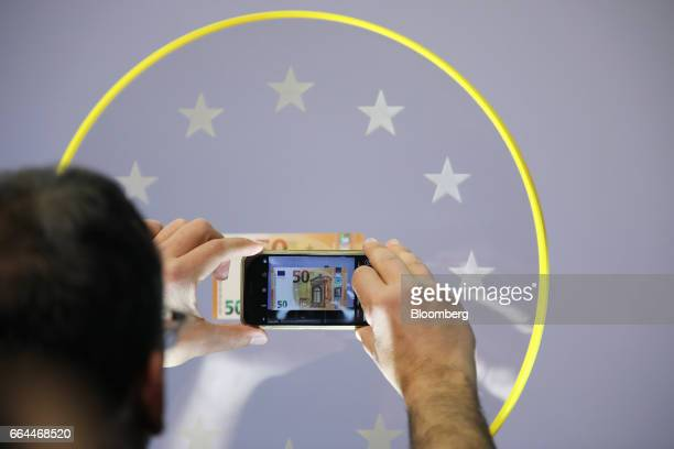 An attendee uses a smartphone to photograph a new 50 euro currency bank note during its unveiling at the European Central Bank headquarters in...