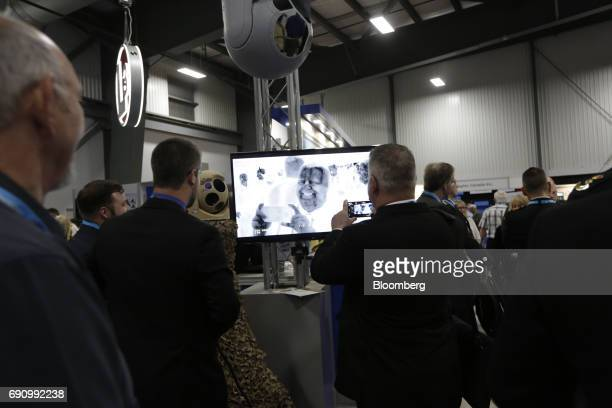 An attendee uses a smartphone to take a photograph of his thermal image on a Wescam Inc MXRSTA imaging system at the company's booth during CANSEC...