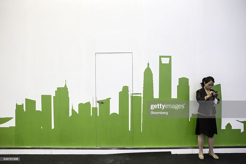 An attendee uses a smartphone while standing in front of a wall featuring Shanghai's skyline at the Mobile World Congress Shanghai in Shanghai, China, on Thursday, June 30, 2016. The exhibition runs until July 1. Photographer: Qilai Shen/Bloomberg via Getty Images