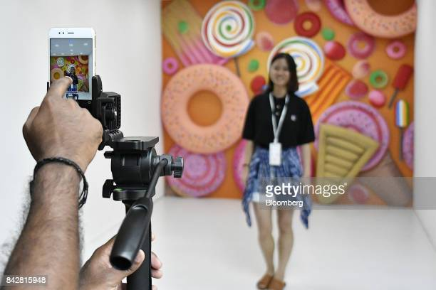 An attendee uses a Xiaomi Corp Mi A1 dual camera device to take a photograph during the smartphone's launch in New Delhi India on Tuesday Sept 5 2017...
