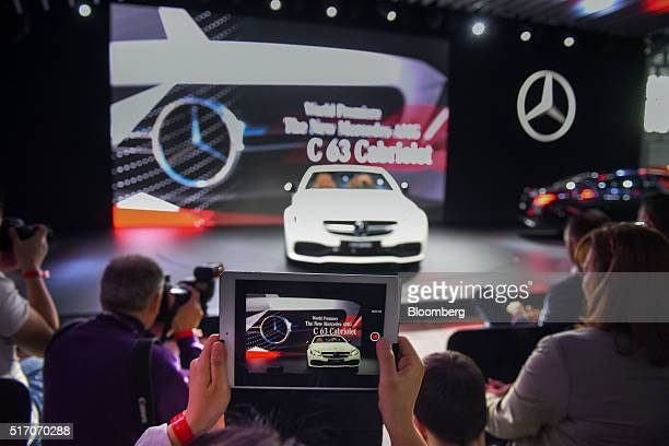 An attendee uses an Apple Inc iPad to photograph the 2017 MercedesAMG C63 Cabriolet convertible vehicle during the 2016 New York International Auto...