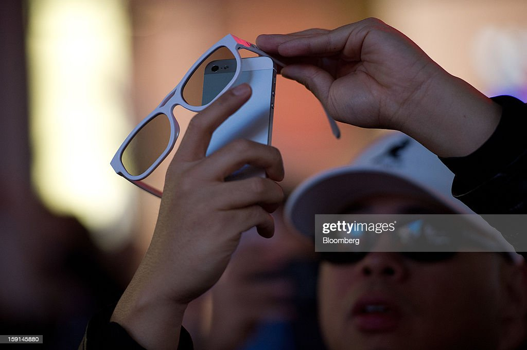 An attendee uses an Apple Inc. iPhone 5 to shoot a video through 3D glasses during a video presentation at the LG Electronics Inc. booth at the 2013 Consumer Electronics Show in Las Vegas, Nevada, U.S., on Tuesday, Jan. 8, 2013. The 2013 CES trade show, which runs until Jan. 11, is the world's largest annual innovation event that offers an array of entrepreneur focused exhibits, events and conference sessions for technology entrepreneurs. Photographer: David Paul Morris/Bloomberg via Getty Images