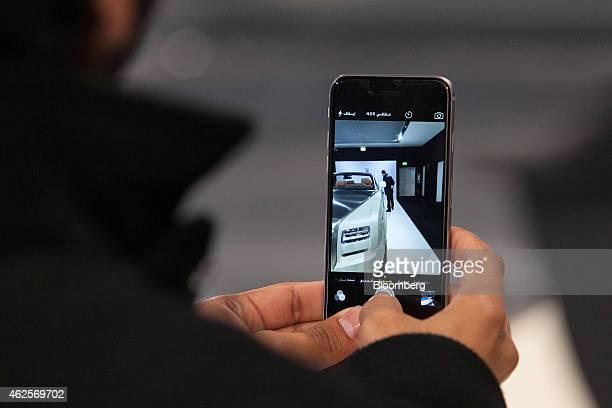 An attendee uses an Apple Inc iPhone to photograph a RollsRoyce Phantom Drophead Coupe automobile inside RollsRoyce Motor Cars Ltd's studio in Berlin...