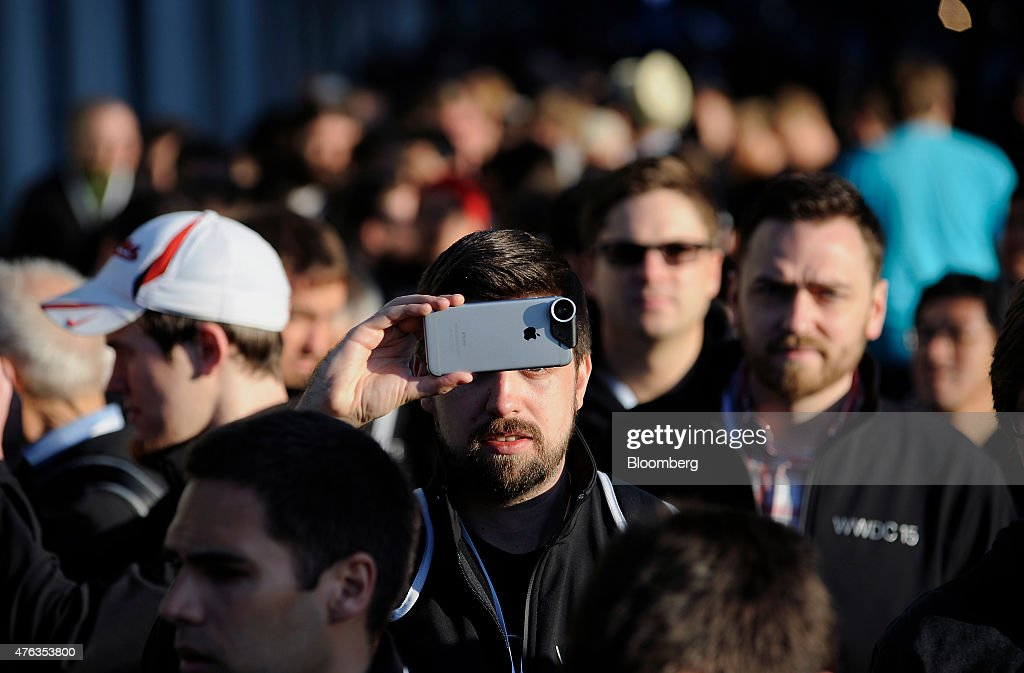 An attendee uses an Apple Inc iPhone to take a photo outside of the Moscone Center before the start of the Apple World Wide Developers Conference in...