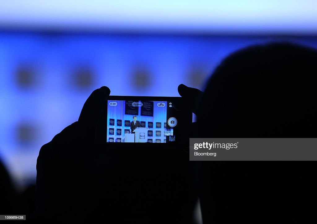 An attendee uses an Apple Inc. iPhone to take a photograph of David Cameron, U.K. prime minister, speaking during a session on day two of the World Economic Forum (WEF) in Davos, Switzerland, on Thursday, Jan. 24, 2013. World leaders, influential executives, bankers and policy makers attend the 43rd annual meeting of the World Economic Forum in Davos, the five day event runs from Jan. 23-27. Photographer: Chris Ratcliffe/Bloomberg via Getty Images