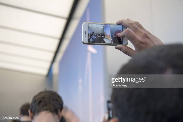 An attendee uses an Apple Inc iPhone to video tape former US Vice President Al Gore chairman and president of Generation Investment Management LLP as...