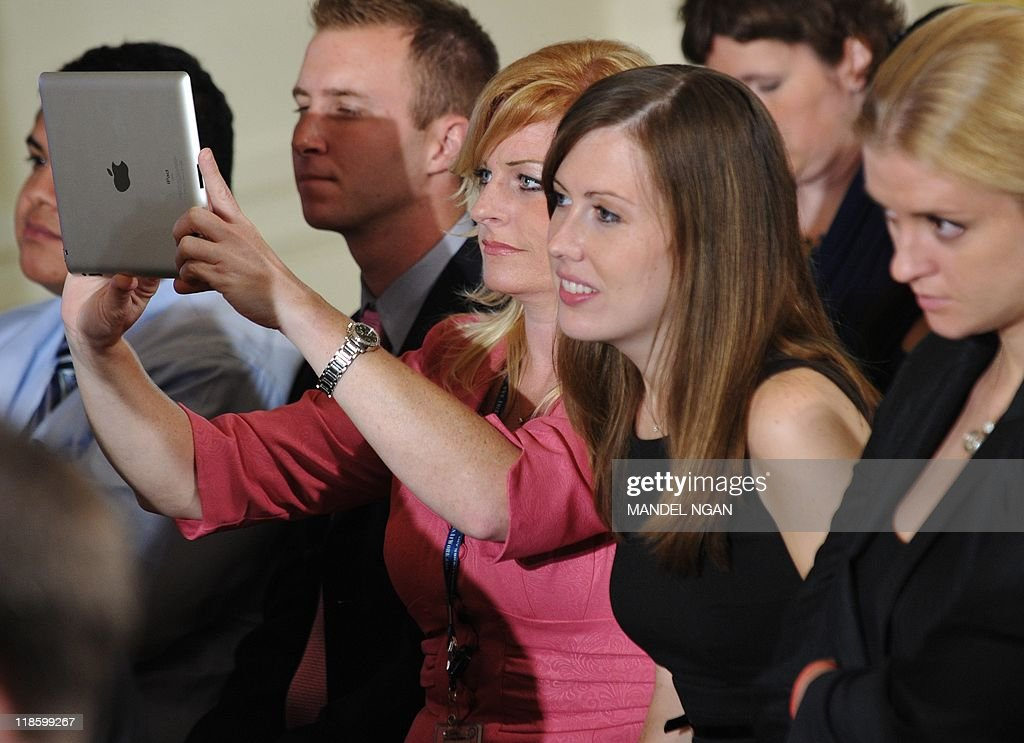 An attendee uses an iPad during a 'Twitter Town Hall' held by US president Barack Obama July 6, 2011 in the East Room of the White House in Washington, DC. AFP PHOTO/Mandel NGAN