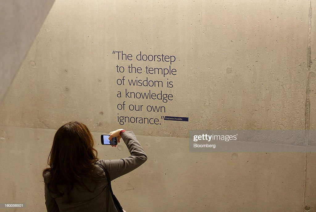 An attendee uses her mobile to take a photograph of a quote on a wall inside of the Congress Center on day three of the World Economic Forum (WEF) in Davos, Switzerland, on Friday, Jan. 25, 2013. World leaders, influential executives, bankers and policy makers attend the 43rd annual meeting of the World Economic Forum in Davos, the five day event runs from Jan. 23-27. Photographer: Simon Dawson/Bloomberg via Getty Images