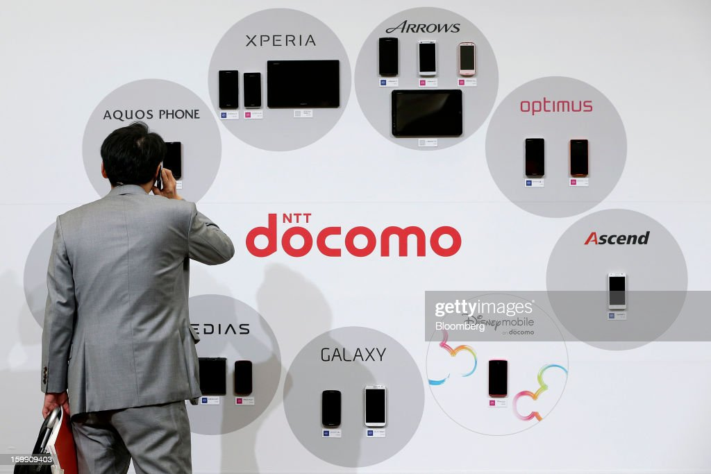 An attendee uses his mobile phone as he looks at the selection of NTT DoCoMo Inc.'s new smartphones and tablet devices during a product launch in Tokyo, Japan, on Tuesday, Jan. 22, 2013. NTT DoCoMo, Japan's biggest mobile-phone company, released their latest tablet and smartphone series on Jan. 22. Photographer: Kiyoshi Ota/Bloomberg via Getty Images