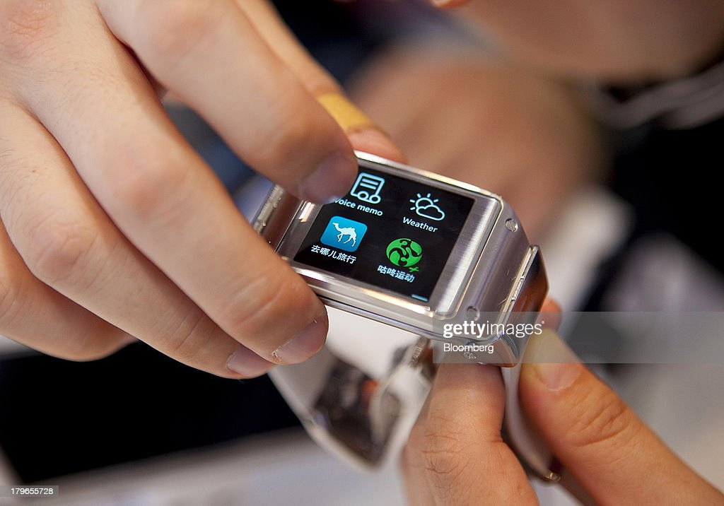 An attendee uses the touch screen of a Galaxy Gear smart watch device, manufactured by Samsung Electronics Co., in this arranged photograph at the IFA consumer electronics show in Berlin, Germany, on Friday, Sept. 6, 2013. Global smartphone revenue will rise 22 percent in 2013, or nearly half the pace of an expected 41 percent gain in shipments, amid falling prices, according to UBS. Photographer: Krisztian Bocsi/Bloomberg via Getty Images