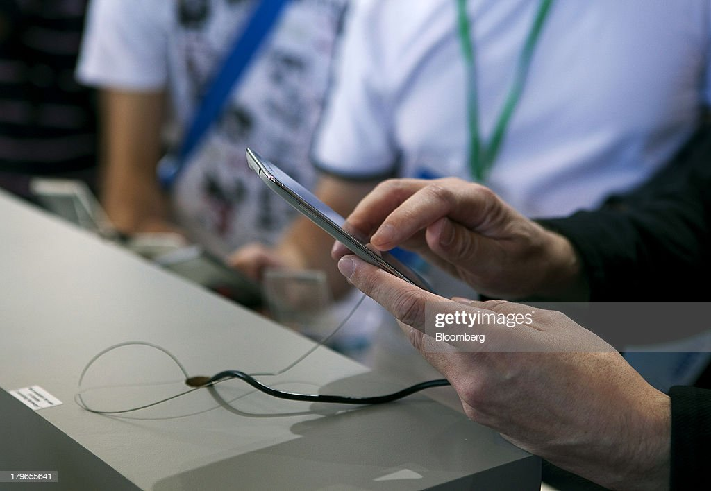 An attendee uses the touchscreen of a Vibe X smartphone device, manufactured by Lenovo Group Ltd., at the IFA consumer electronics show in Berlin, Germany, on Friday, Sept. 6, 2013. Global smartphone revenue will rise 22 percent in 2013, or nearly half the pace of an expected 41 percent gain in shipments, amid falling prices, according to UBS. Photographer: Krisztian Bocsi/Bloomberg via Getty Images