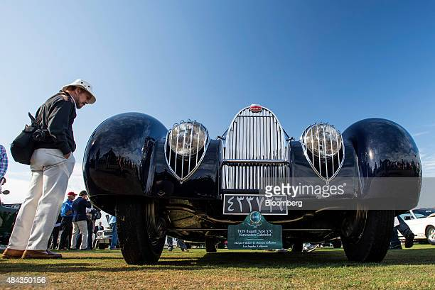 An attendee views a 1939 Bugatti Automobiles SAS Type 57C Vanvooren Cabriolet vehicle displayed during the 2015 Pebble Beach Concours d'Elegance in...
