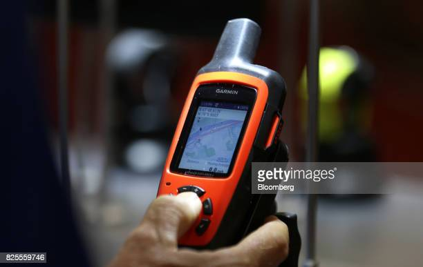 An attendee views a Garmin Ltd inReach satellite device on display during the Outdoor Retailer Summer Market Show in Salt Lake City Utah US on...