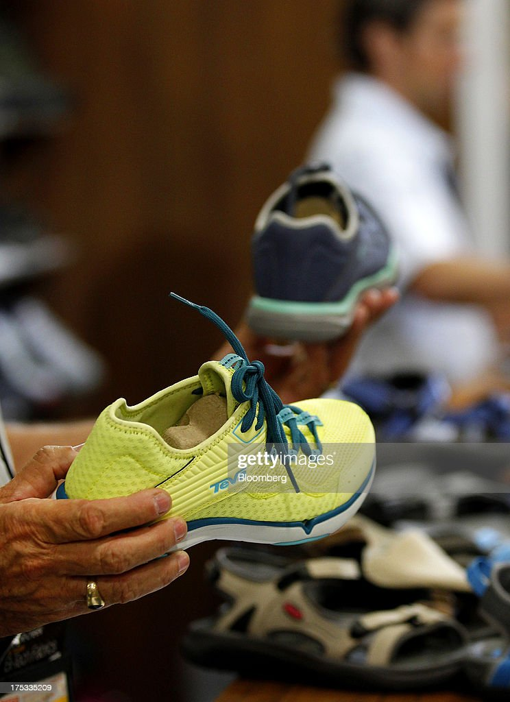 An attendee views Deckers Outdoor Corp. Teva brand sneakers at the company's booth during the Outdoor Retailer Summer Market show in Salt Lake City, Utah, U.S., on Thursday, Aug. 1, 2013. Consumer spending in the U.S. rose in line with forecasts in June as Americans' incomes grew, a sign the biggest part of the economy is withstanding fiscal headwinds. Photographer: George Frey/Bloomberg via Getty Images