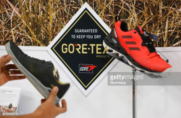 An attendee views GoreTex Inc sneakers on display during the Outdoor Retailer Summer Market Show in Salt Lake City Utah US on Saturday July 29 2017...