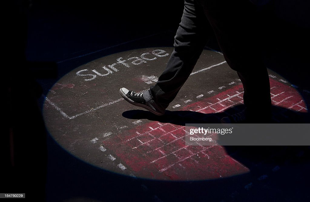An attendee walks over a chalk rendering a Microsoft Corp. Surface tablet computer during an event in New York, U.S., on Thursday, Oct. 25, 2012. Microsoft Corp. will be constrained in a contest against Apple Inc. in the market for handheld computers by unveiling a tablet that doesn't work with some of the most widely used downloadable applications. Photographer: Scott Eells/Bloomberg via Getty Images