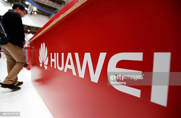 An attendee walks past a Huawei Technologies Co sign displayed at a booth at the CuttingEdge IT Electronics Comprehensive Exhibition at Makuhari...