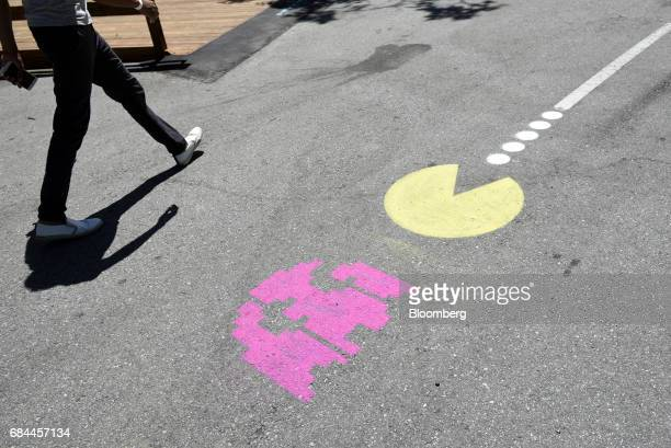 An attendee walks past a PacMan logo painted on the ground at the Google I/O Annual Developers Conference in Mountain View California US on Wednesday...