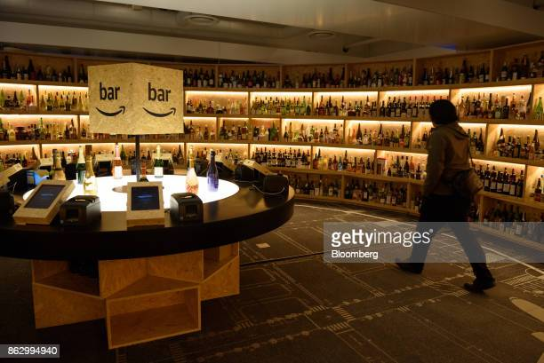 An attendee walks past bottles of liquor at the Amazon Bar operated by Amazon Japan KK during a media preview in Tokyo Japan on Thursday Oct 19 2017...