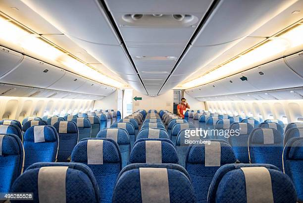 An attendee walks through an aisle on board a Boeing Co 777300 aircraft operated by Cathay Pacific Airways Ltd during an event at the Hong Kong...