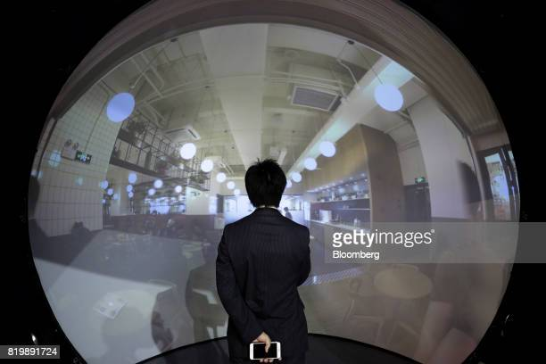 An attendee watches imagery of WeWork's coworking and office spaces in Shanghai captured with a 360degree camera at the annual SoftBank World 2017...