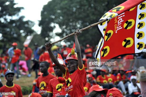 An attendee waves a campaign flag during a presidential election rally for the Jubilee Party in Nairobi Kenya on Friday Aug 4 2017 The winner of...