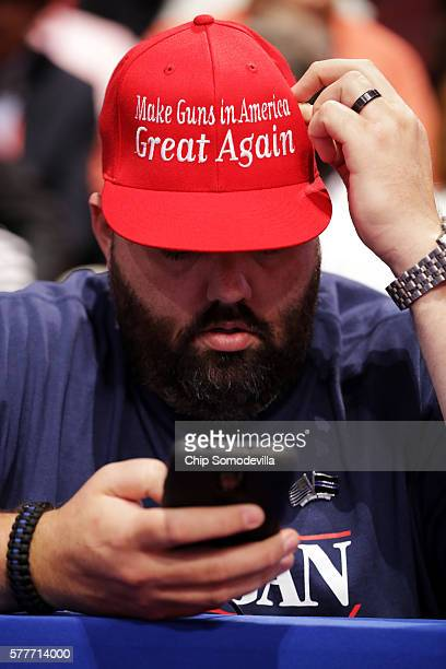 An attendee wearing a hat the reads 'Make Guns in America Great Again' looks at his phone during the second day of the Republican National Convention...