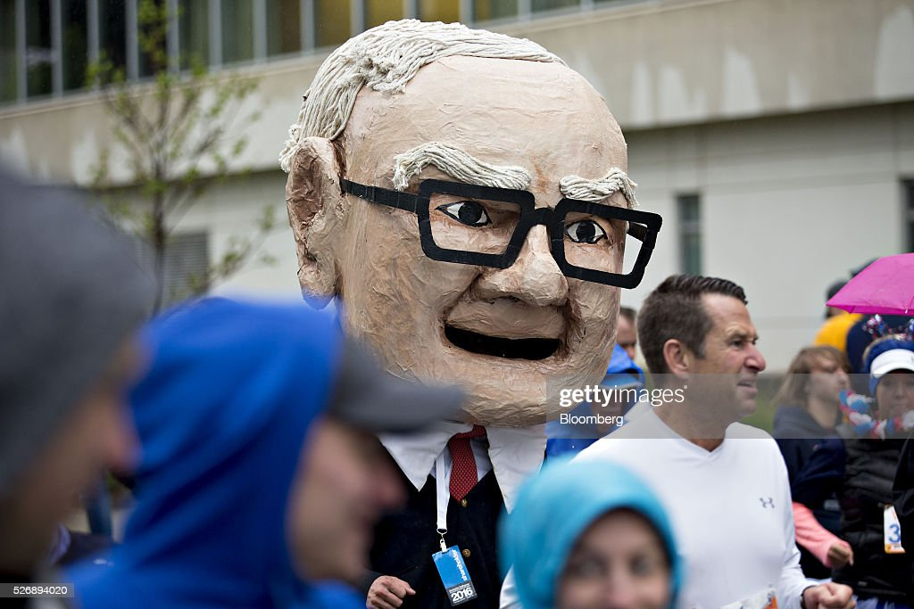 An attendee wearing a large head in the likeness of Warren Buffett, chairman and chief executive officer of Berkshire Hathaway Inc., runs at the start of the 'Berkshire Hathaway Invest In Yourself 5K' race presented by Brooks Sports, Inc., a Berkshire company, on the sidelines the Berkshire Hathaway annual shareholders meeting in Omaha, Nebraska, U.S., on Sunday, May 1, 2016. Dozens of Berkshire Hathaway subsidiaries will be showing off their products as Chief Executive Officer Warren Buffett hosts the company's annual meeting. Photographer: Daniel Acker/Bloomberg via Getty Images