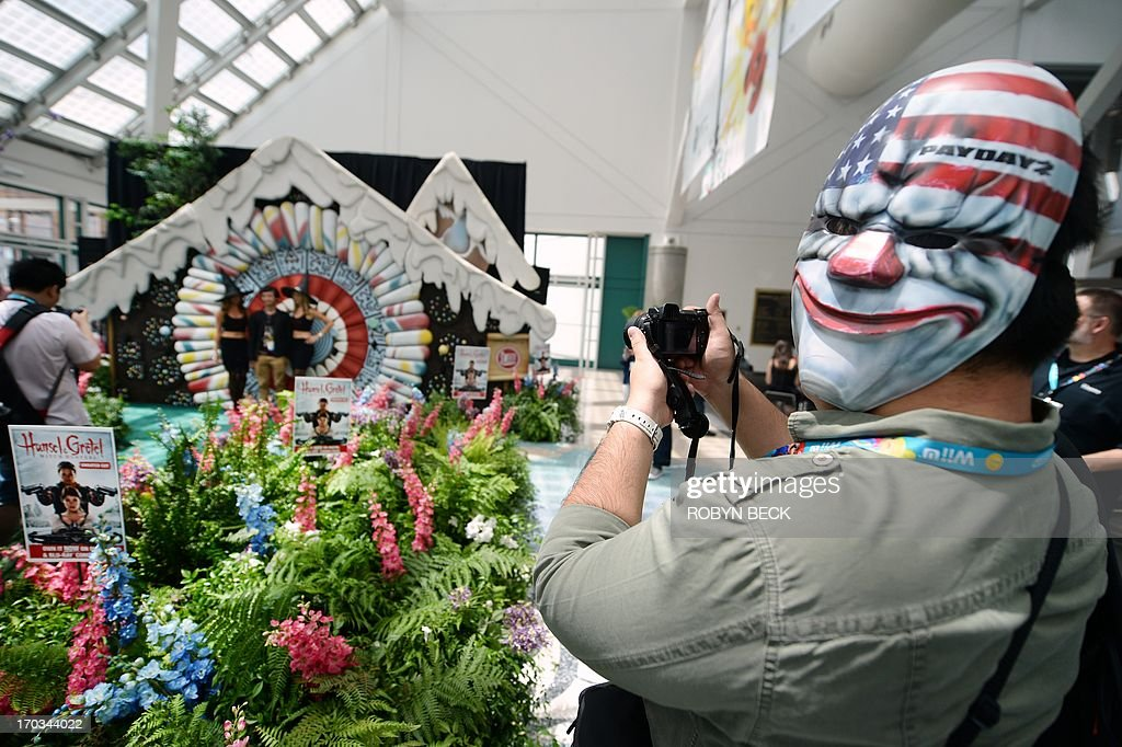 An attendee wearing a mask for the 'Payday 2' first-person shooter video game by Overkill Software snaps a photo of the 'Hansel and Gretel Witch Hunters' display on the first day of the Electronic Entertainment Expo (E3) in Los Angeles on June 11, 2013. The Electronic Entertainment Expo (E3), an annual trade fair for the computer and video games industry, runs from June 11-13.