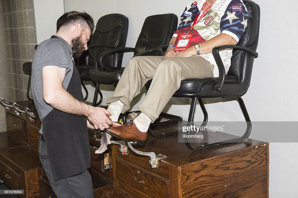 An attendee wearing an American flag themed shirt gets a shoe shine during the 2016 Texas Republican Convention in Dallas Texas US on Saturday May 14...