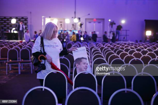 An attendee wearing an Andrew Scheer member of parliament and Conservative Party leader candidate shirt carries a campaign sign while walking through...