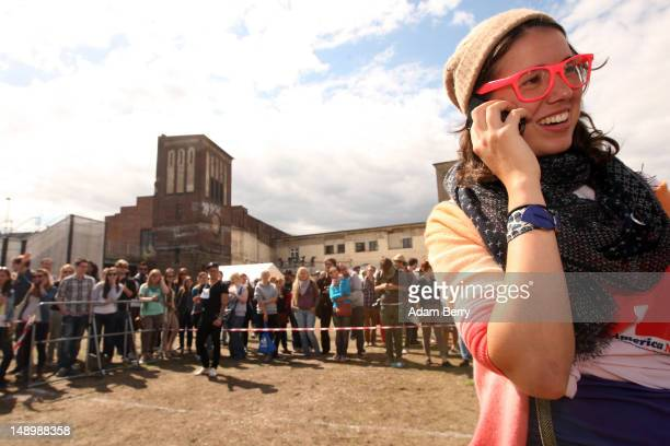 An attendee wearing pink glasses speaks on a mobile phone during the second annual Hipster Olympics on July 21 2012 in Berlin Germany With events...