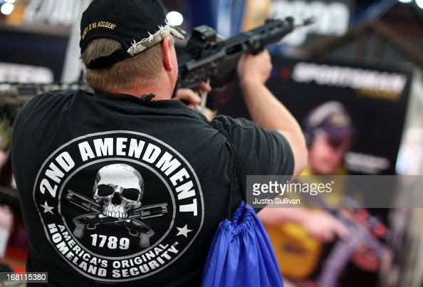 An attendee wears a 2nd amendment shirt while inspecting an assault rifle during the 2013 NRA Annual Meeting and Exhibits at the George R Brown...
