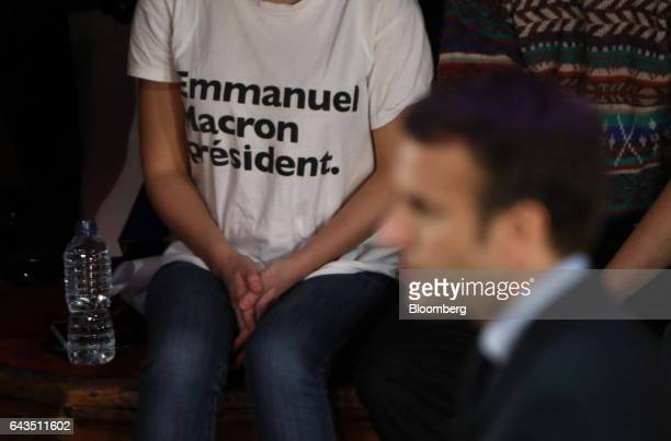 An attendee wears a campaign tshirt as Emmanuel Macron French presidential candidate right speaks at a campaign meeting with French expatriates at...