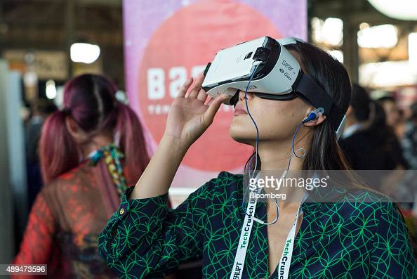 An attendee wears a Galaxy Gear VirtualReality headset in Startup Alley during the TechCrunch Disrupt SF 2015 conference in San Francisco California...