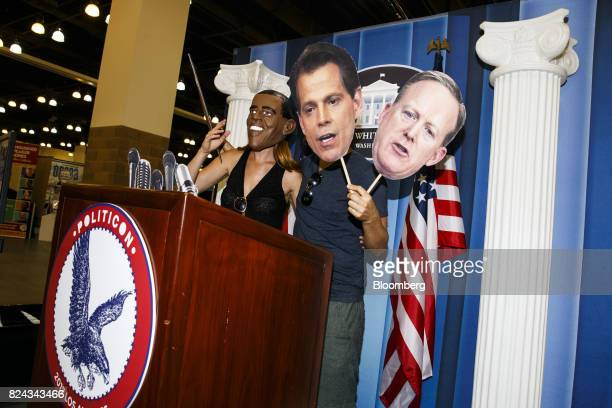 An attendee wears a mask in the likeness of former US President Barack Obama left as another attendee holds cardboard faces of Anthony Scaramucci...