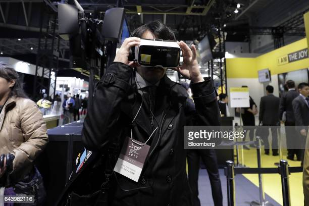 An attendee wears a virtual reality headset with a smartphone installed to view the images taken with a Nikon Corp KeyMission 360 4Kcapable 360degree...
