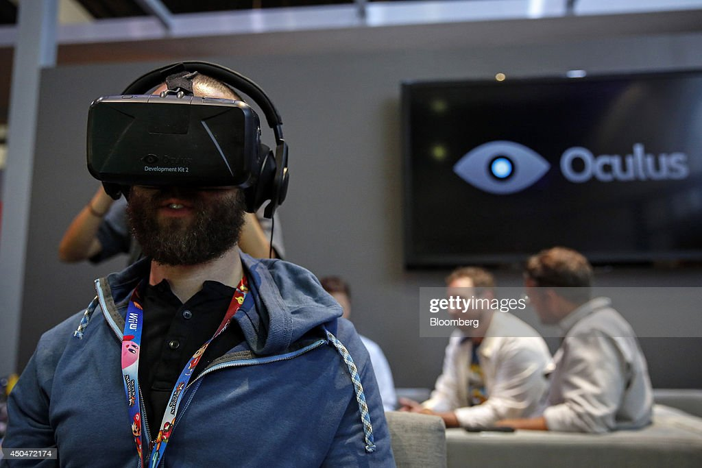 An attendee wears an Oculus VR Inc. Rift Development Kit 2 headset to play a video game during the E3 Electronic Entertainment Expo in Los Angeles, California, U.S., on Wednesday, June 11, 2014. E3, a trade show for computer and video games, draws professionals to experience the future of interactive entertainment as well as to see new technologies and never-before-seen products. Photographer: Patrick T. Fallon/Bloomberg via Getty Images