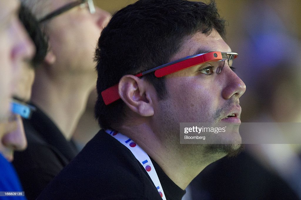 An attendee wears Google Project Glass while listening to a keynote speech during the Google I/O Annual Developers Conference in San Francisco, California, U.S., on Wednesday, May 15, 2013. Google Inc. introduced a subscription music-streaming service, one of several product updates to be unveiled at a developer meeting this week as the search provider seeks to attract more users and advertisers. Photographer: David Paul Morris/Bloomberg via Getty Images