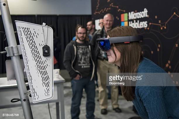 An attendee wears the Microsoft Corp HoloLens augmented reality viewer while having her photograph taken at the Microsoft Developers Build Conference...