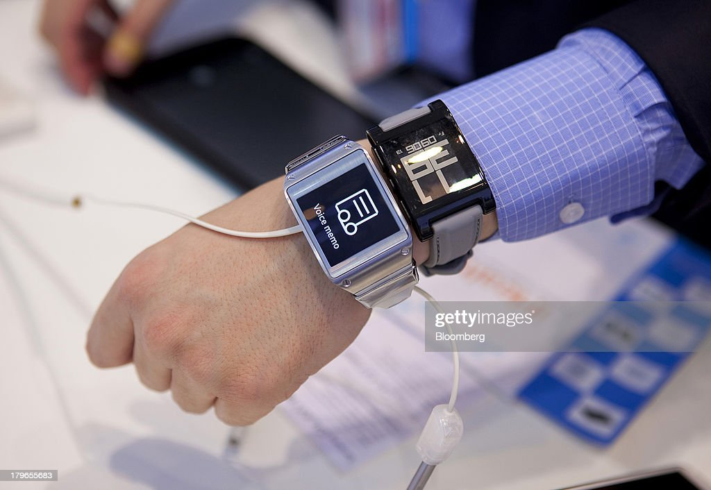 An attendee wears two Galaxy Gear smart watches, manufactured by Samsung Electronics Co., in this arranged photograph at the IFA consumer electronics show in Berlin, Germany, on Friday, Sept. 6, 2013. Global smartphone revenue will rise 22 percent in 2013, or nearly half the pace of an expected 41 percent gain in shipments, amid falling prices, according to UBS. Photographer: Krisztian Bocsi/Bloomberg via Getty Images