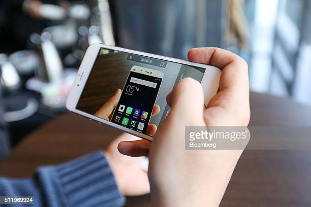 An attendees films Mi5 smartphone manufactured by Xiaomi Corp during its launch at the Mobile World Congress in Barcelona Spain on Wednesday Feb 24...