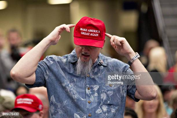 An attenedee points to a 'Make America Great Again' hat while waiting for the start of a rally with US President Donald Trump in Cedar Rapids Iowa US...