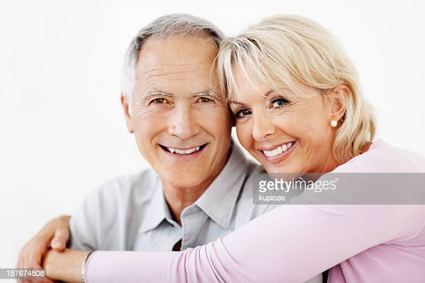 An attractive mature woman embracing senior man against white
